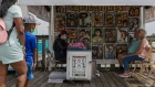 A caricature artist draws the image of a couple while customers wait in line at a vendor stall at Broadway at the Beach in Myrtle Beach, South Carolina. Photographer: Micah Green/Bloomberg
