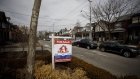 "A ""For Sale"" sign sits in front of a home in Toronto on March 11, 2021."