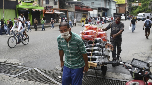 Workers wearing protective masks pull a cart in the Petare neighborhood of Caracas, Venezuela, on Thursday, Sept. 3, 2020. After a dip in late August, Venezuela is seeing an uptick of daily cases as the country nears 50,000 infections. Photographer: Carlos Becerra/Bloomberg