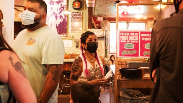Customers and employees wear protective masks at a taco bar in Austin, Texas. Photographer: Mary Kang/Bloomberg