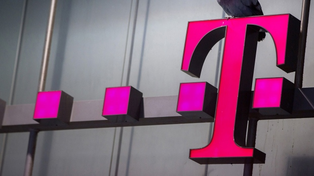A pigeon rests on a T-Mobile logo outside a mobile phone store, operated by Deutsche Telekom AG, in Munich, Germany Photographer: Krisztian Bocsi/Bloomberg