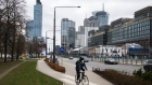 A cyclist uses a cycle lane near offices and skyscrapers in the financial district in Warsaw, Poland, on Tuesday, April 6, 2021. Poland's Central Bank's Monetary Policy Council meets on Wednesday to set policy after the economy was hit with new restrictions in March to stop the spread of the Coronavirus pandemic.