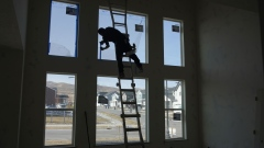 A contractor tapes a window before painting the interior of a house under construction in Lehi, Utah. Photographer: George Frey/Bloomberg