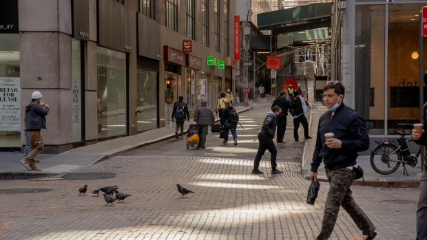 Pedestrians walk along a street in the Financial District of New York, U.S., on Wednesday, May 12, 2021. With 37% of Manha