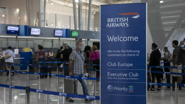 A British Airways Plc sign stands in front of travelers queuing at check-in counters at Athens International Airport, in Athens, Greece, on Thursday, Sept. 17, 2020. The U.K. government imposed a 14-day quarantine for travelers arriving from seven Greek islands, starting from Sept. 7, in a shift to its coronavirus strategy, as domestic cases of the disease continued to rise. Photographer: Yorgos Karahalis/Bloomberg