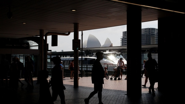 Pedestrians are silhouetted as they walk along a sidewalk at Circular Quay in Sydney, Australia, on Friday, Jan. 11, 2019. Australian consumer confidence slumped the most in more than three years, amid pessimism over falling property prices and economic growth, after the nation's dollar tumbled to the weakest in almost 10 years at the beginning of the month. Photographer: Lisa Maree Williams/Bloomberg