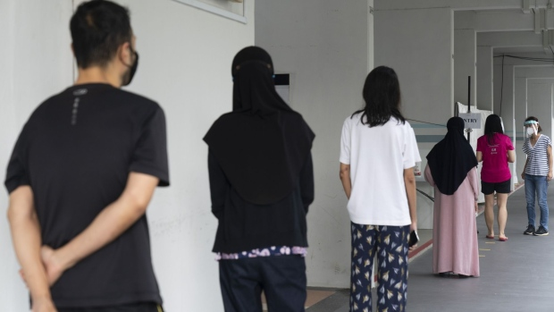 People wearing protective masks stand in line outside a mandatory Covid-19 test site set up at a housing block in the Hougang district of Singapore, on Saturday, May 22, 2021. Singapore is stepping up mandatory testing across the island-nation for Covid-19 as new and unlinked infections rise in the local community. The government is conducting tests for all residents of the housing block after some positive coronavirus cases were found there.