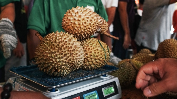 A vendor weighs Musang King durians during the Malaysia International Durian Festival.