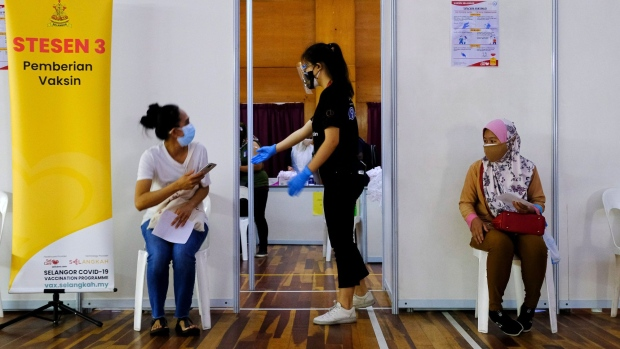 A health worker speaks to a a member of the public waiting to receive the Sinovac Biotech Covid-19 vaccine at a vaccination center set up at the PKNS Sports Complex in Kelana Jaya, Selangor, Malaysia, on Wednesday, Aug. 11, 2021. Malaysia has eased virus restrictions for those who have completed the full vaccination regime, allowing them to cross state borders and dine at restaurants as authorities seek to re-open the economy.
