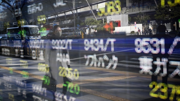 A pedestrian is reflected in an electronic stock board outside a securities firm in Tokyo. Photographer: Noriko Hayashi/Bloomberg
