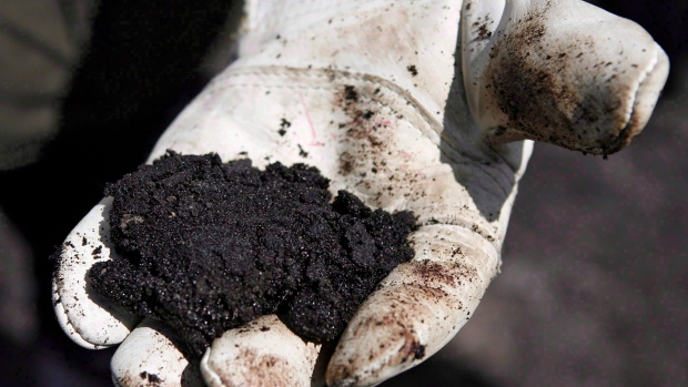 An oil worker holds raw sand bitumen near Fort McMurray. condensate.