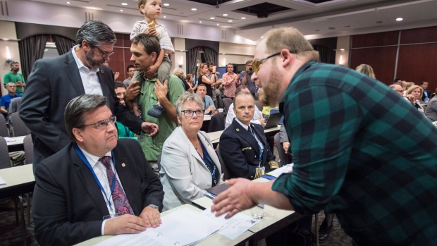 A demonstrator confronts Montreal mayor Denis Coderre at the NEB Energy East hearing