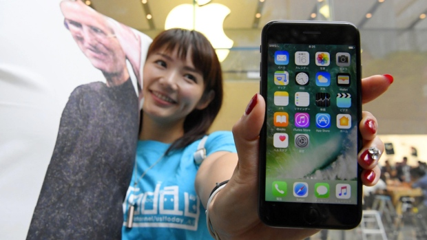 A woman poses with Apple's iPhone 7 after purchasing it in Tokyo