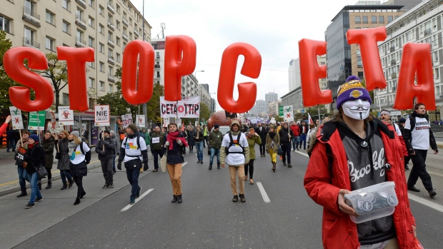 Protesters march against trade deals with Canada and the U.S. in Warsaw, Poland, Saturday, Oct. 15.
