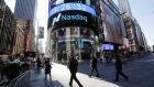 People walk past the Nasdaq MarketSite in New York