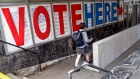 A woman passes a large sign as she arrives to vote early on Friday, Sept. 23, 2016, in Minneapolis.