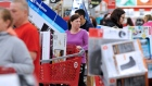 A woman maneuvers her way through Black Friday shoppers at the Target store in Plainville, Mass.