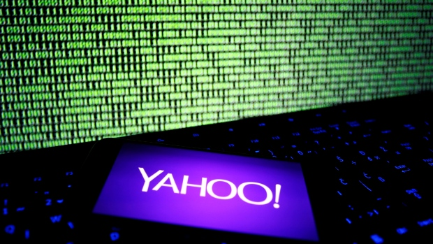 A photo illustration shows a Yahoo logo on a smartphone in front of a displayed cyber code