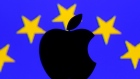 A 3D printed Apple logo is seen in front of a displayed European Union flag