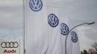 A logo of Audi is pictured next to flags with logos of VW at a car shop in Germany