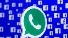 A 3D printed Whatsapp logo is seen in front of Facebook's logo