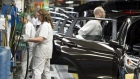 Production Associates inspect cars moving along assembly line at Honda manufacturing plant