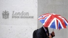 A worker shelters from the rain under a Union Flag umbrella as he passes the London Stock Exchange i