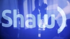 A television cameraman is reflected on a television screen displaying the Shaw logo