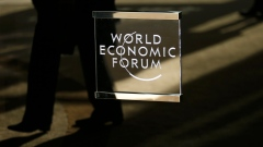 A man walks past the official logo of the World Economic Forum (WEF) in Davos, Switzerland