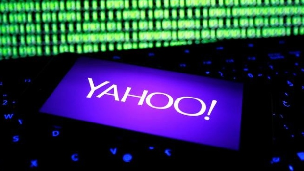 Yahoo logo on a smartphone in front of a displayed cyber code