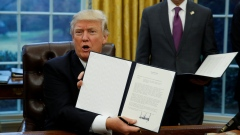 U.S. President Donald Trump holds up the executive order on withdrawal from TPP
