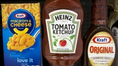 A Heinz Ketchup bottle sits between a box of Kraft macaroni & cheese and a bottle of Kraft Original