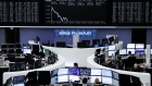 Traders work at their desks in front of the German share price index, DAX board in Frankfurt