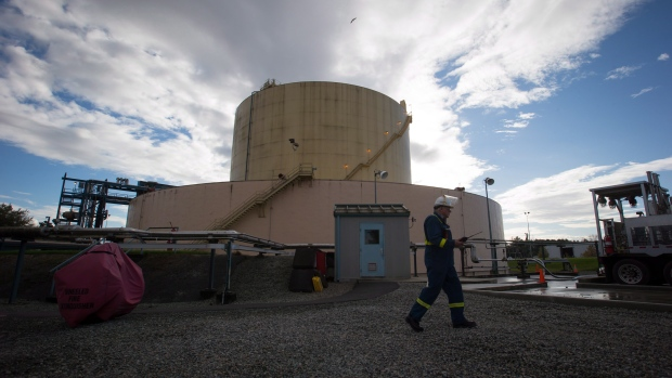A FortisBC employee walks past a storage tank at the existing Tilbury LNG facility