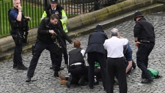 A man treated by emergency services as police look on at the scene outside the Houses of Parliameent