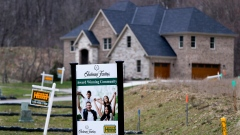Real estate signs mark the lots near one of the new homes for sale in in Cranberry Township, Pa.