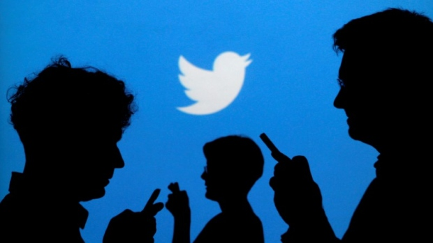 People holding phones are silhouetted against a backdrop projected with the Twitter logo