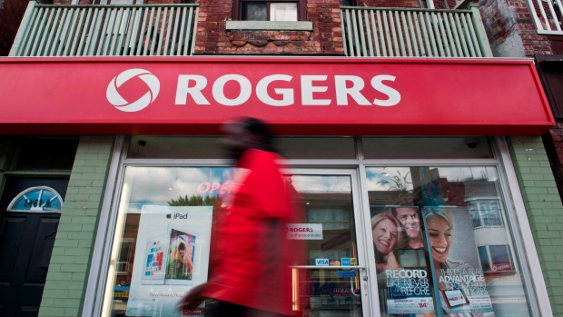 A man walks by a Rogers store in Toronto