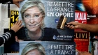 Members of the French National Front political party paste a poster for leader Marine Le Pen.