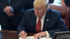 President Donald Trump signs an executive memorandum on investigation of steel imports on April 20