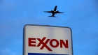 An airplane comes in for a landing above an Exxon sign at a gas station in Norridge, Illinois