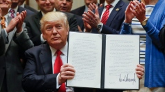 Trump holds up the signed executive order to expand ocean oil drilling