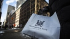 A woman holds a Hudson's Bay shopping bag in front of the HBC flagship department store in Toronto