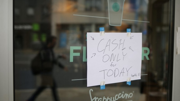 A sign saying electronic payments are not functioning is seen in front of a Toronto Starbucks