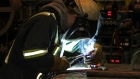 A worker uses a welding torch at Champion Iron's Bloom Lake mine near Fermont