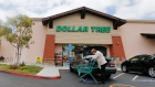 A shopper searches her purse outside a Dollar Tree store in Encinitas, Calif. Dollar Tree