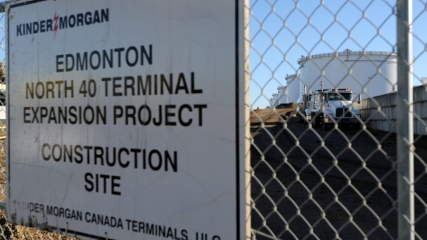 Dump trucks are parked near crude oil tanks at Kinder Morgan's North 40 terminal expansion construction project in Sherwood Park
