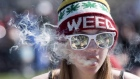 A woman exhales while smoking a joint during the annual 420 marijuana rally on Parliament Hill
