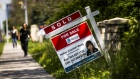 "A woman walks towards a ""for sale"" sign of a home that has been sold in Toronto, Canada."