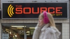 A woman talks on her cell phone as she walks past a The Source store in Ottawa.